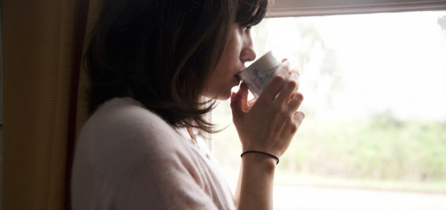 WomanLookingOutWindowDrinkingTeaInMorning-850x400