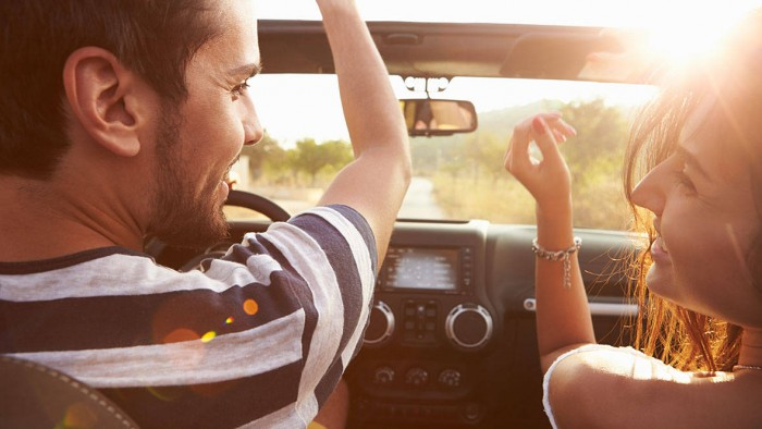 Young-Couple-Driving-Along-Country-Road-In-Open-Top-Car