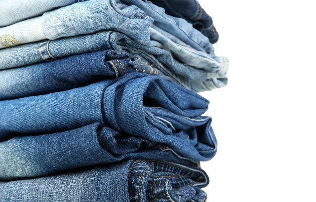 Lot of different blue jeans close-up isolated on white; Shutterstock ID 114997642; PO: aol; Job: production; Client: drone