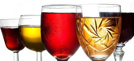 A collection of different glasses filled with different liquids isolated on a white background.