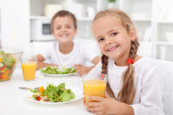 Kids eating a healthy meal in the kitchen