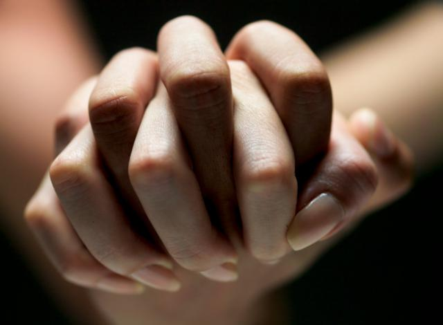 Two hands clasp each other