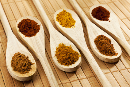Six wooden kitchen spoons with heaps of nutmeg, curry, red pepper and cinnamon