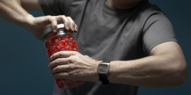 Mature man opening jar of candies, mid section (focus on hands)