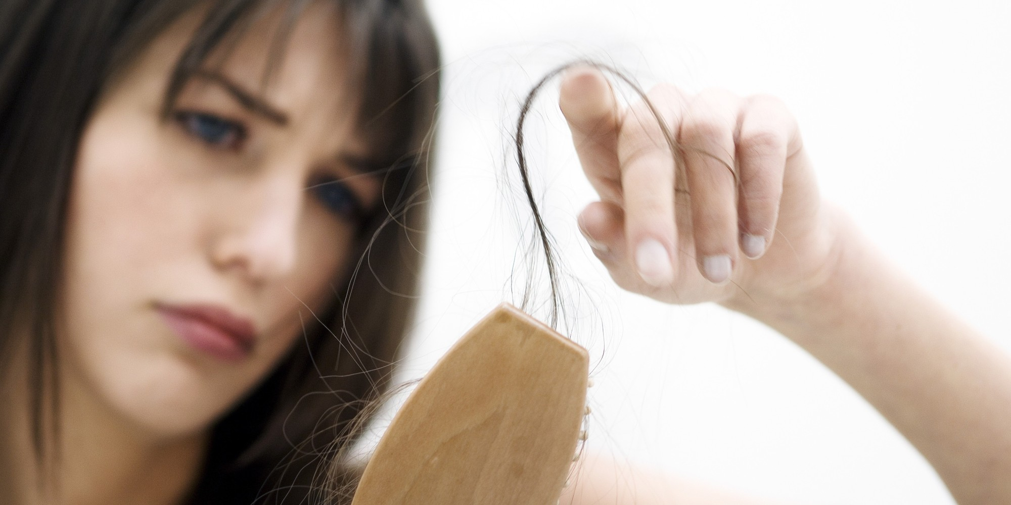 Portrait of a young woman brushing her hair, close up (studio)